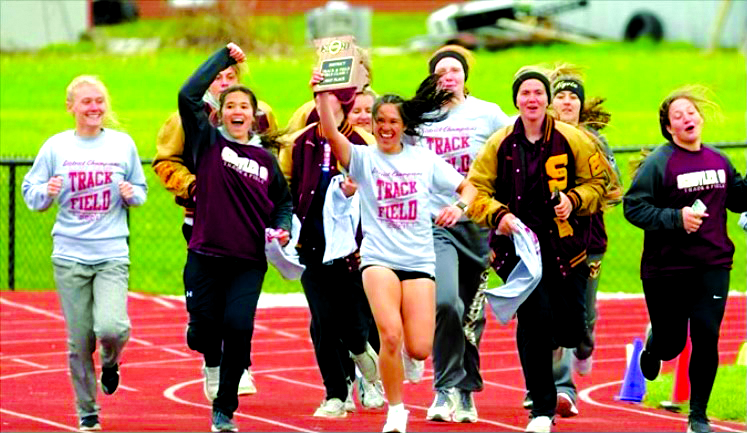 The Lady Rams track team, led by seniors Emma and Lexi Clifford, taking their victory lap with the District first place plaque in hand.